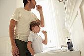 Father and son (5-7) brushing teeth in bathroom, low angle view