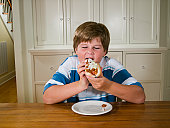 Overweight boy (10-11) sitting at table eating hot dog
