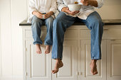 Father and son sitting on kitchen counter eating breakfast