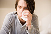 Sick man wiping nose with tissue