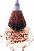 Eyeshadow brush above disc of eyeshadow powder, close-up