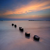 Tranquil Seascape with Old Wooden Posts at Sunset