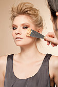 Portrait of young woman having make up applied by trowel