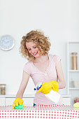 Gorgeous red-haired woman cleaning a cutting board in the kitchen