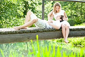 Young couple sitting and relaxing on sunlit footbridge