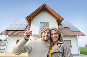 Portrait of couple holding keys to new home