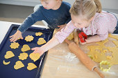 Boy and girl placing cookie shapes on baking tray in kitchen