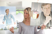 Mid adult woman holding large jigsaw pieces of images of men