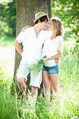 Young couple kissing by tree in summer meadow