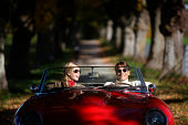 Couple driving in red sports car