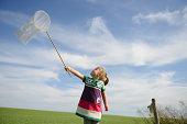 Girl holding up butterfly net against blue sky