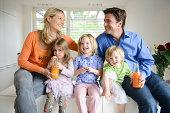 Family sitting on kitchen worktop drinking orange juice