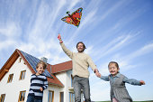 Mid adult man flying kite with son and daughter, low angle view