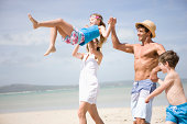 Man and woman swinging daughter on beach