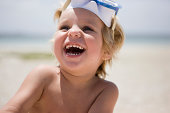 Boy in scuba mask on beach, laughing