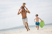 Father and boys running on beach