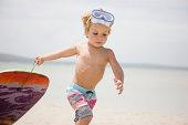 Young boy pulling body board on beach