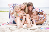 Family wrapped in blanket on beach