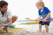 Father and son digging sand on beach
