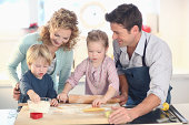 Mother and father helping boy and girl make cookies