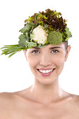 Woman wearing cauliflower and broccoli against white background