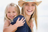 Mother carrying daughter on piggyback, portrait