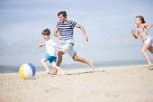 Family running after beach ball on beach