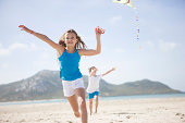 Girl running with kite on beach