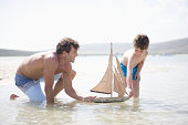 Boy and father playing with toy boat in sea
