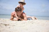 Boy lying on father on beach