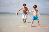 father teaching son how to surf in sea