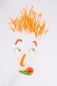 Face made of vegetables against white background