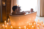 Couple enjoying bath together in candle light