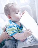 Baby boy holding laptop