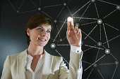 Businesswoman using touch screen, smiling
