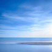 Ocean sandy beach line and blue sunset