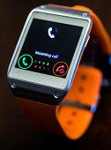 Orange smart watch receiving a call