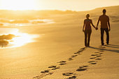 Couple Leaving Behind Track Of Footprints While Walking On Beach