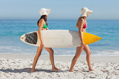 Two attractive women in bikinis holding a surfboard