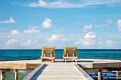 two recliners chairs under on a dock in the Caribbean