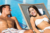Couple relaxing in deck chairs by the swimming pool