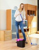 ordinary long-haired girl washing  floor with mop