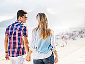Couple walking on coastline.