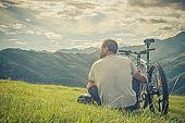 Young man sitting near bike looking at panorama on mountain