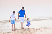 Young father with son and toddler girl at the beach