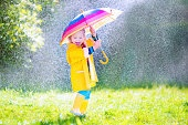 Beautiful funny toddler with umbrella playing in the rain