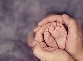 newborn baby legs in parents hands