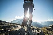 Hiking feet againt sun at mountain peak