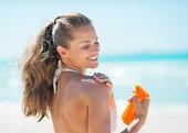 happy young woman applying sun screen creme