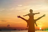 father and son on sunset beach